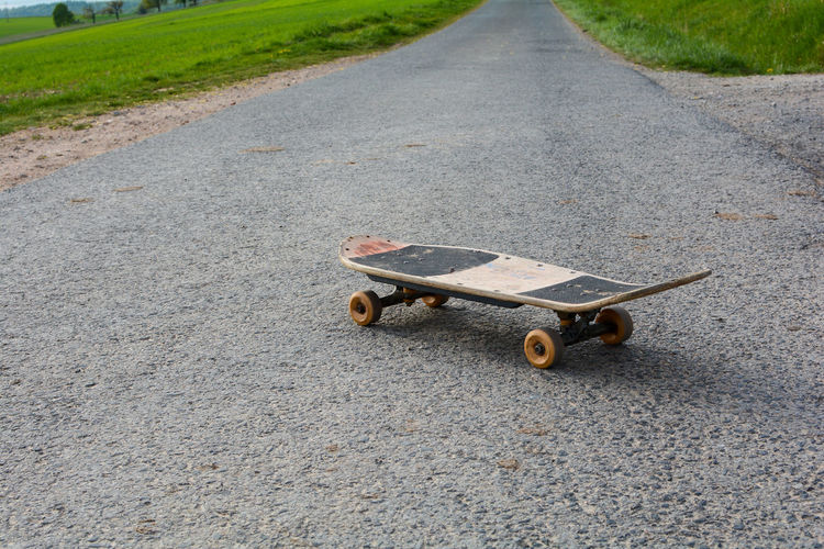 Old skateboard stands on a lonely country road in green nature
