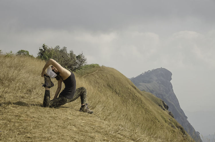 Young girl doing yoga on the mountain. Adventure Beauty In Nature Casual Clothing Cloud Cloud - Sky Cloudy Day Grass Hill Idyllic Landscape Leisure Activity Lifestyles Mountain Nature Outdoors Sky Yoga Yoga In Nature Yoga Pose
