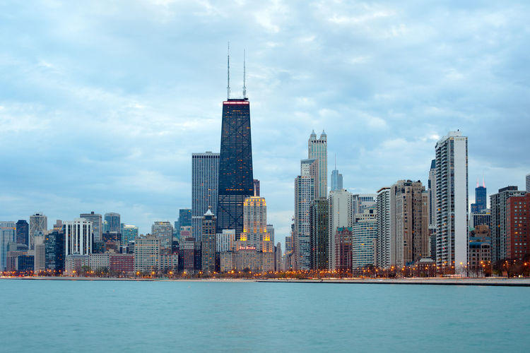 Modern buildings in city against cloudy sky by lake