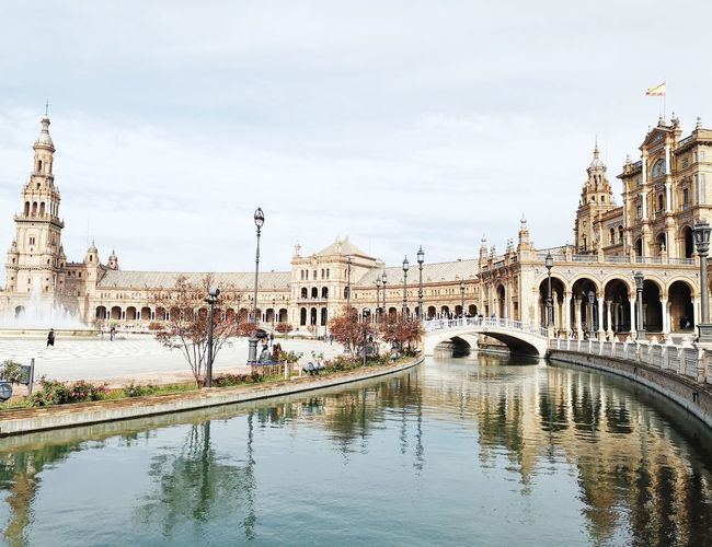 SEVILLA, SPAIN - NOVEMBER 14, 2018 : scenic view of the famous historical Plaza de Espana in Sevilla, must be visited in Sevilla. Famous Place Landmark Landscape Backgrounds Style Travel Destinations Romantic Light Winter_collection World Heritage Historical Building Tourism Destination Attraction City Politics And Government Cityscape Clock Face Water Bridge - Man Made Structure Clock Tower Reflection Sky Architecture Palace Gothic Style Old Town Monument Historic National Monument Pavilion