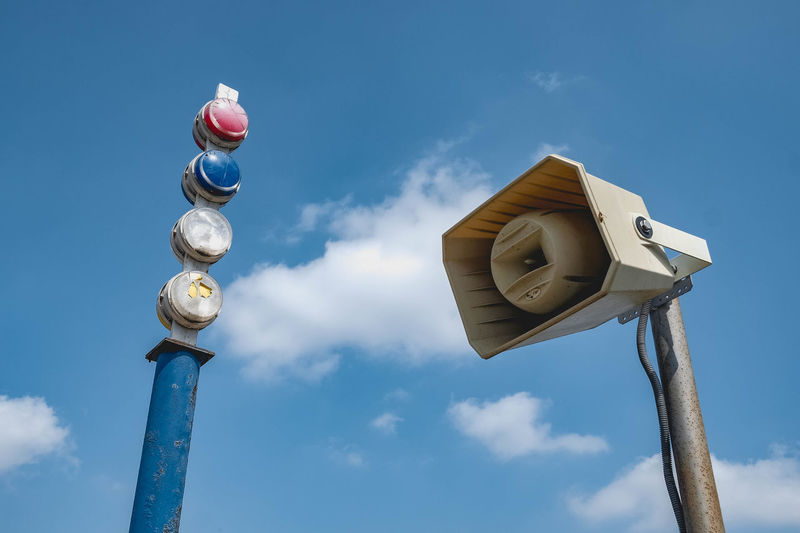 Low angle view of megaphone and lights against sky