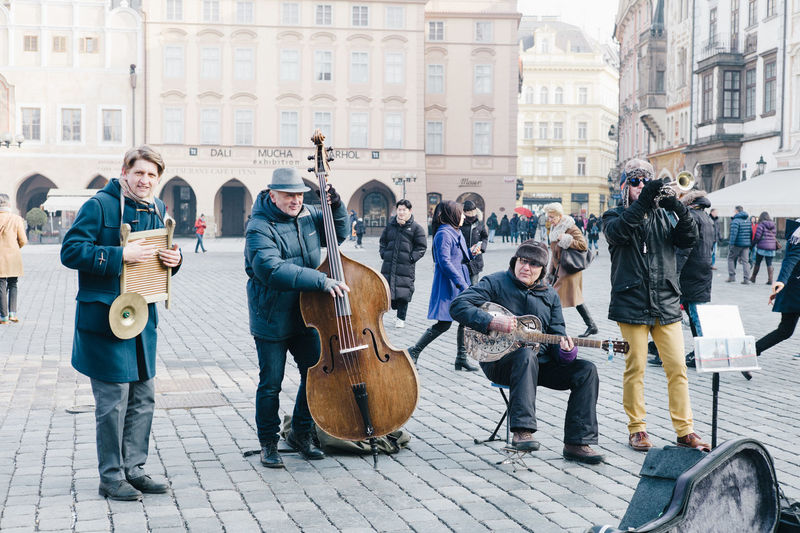 People playing guitar on street in city