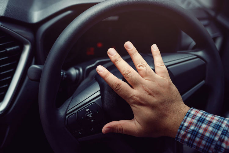 Midsection of man using smart phone in car