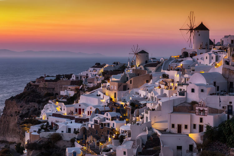The idyllic village of Oia, Santorini, Greece, with the white houses and windmills on top during sunset time Sky Sea Travel Destinations Town House TOWNSCAPE High Angle View Sunset Building Oia Greece Windmill Island Santorini Cyclades White Whitewashed Greek Mediterranean  Europe Travel Tourism Destination Attraction Volcano