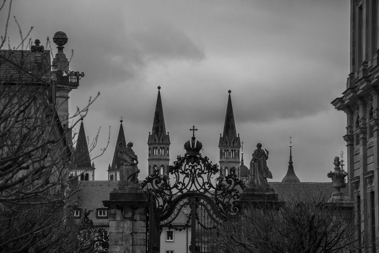 Low angle view of cross on gate against wurzburg cathedral towers