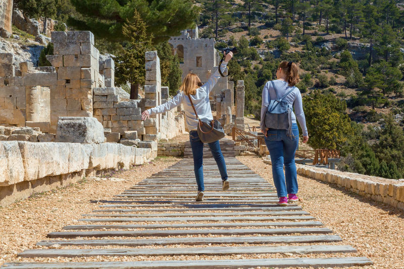 Rear View Of Female Friends On Footpath By Old Ruins
