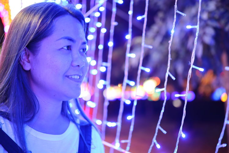 Close-up of smiling woman looking away against illuminated lighting equipment at night