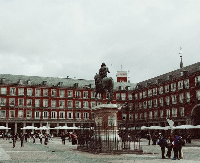 Statue at town square against cloudy sky