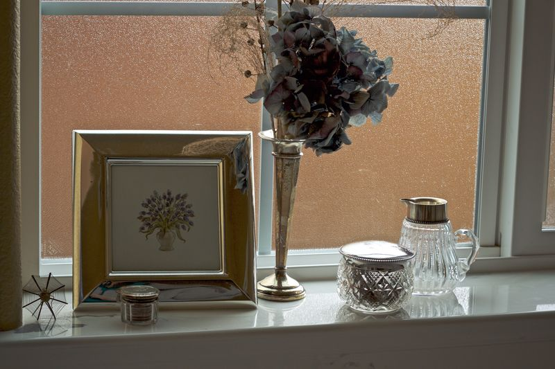 Close-Up Of Picture Frame And Vase On Window Sill At Home