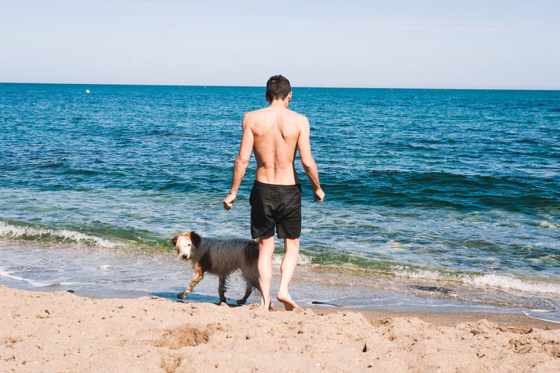 Full length of shirtless man with dog standing on beach