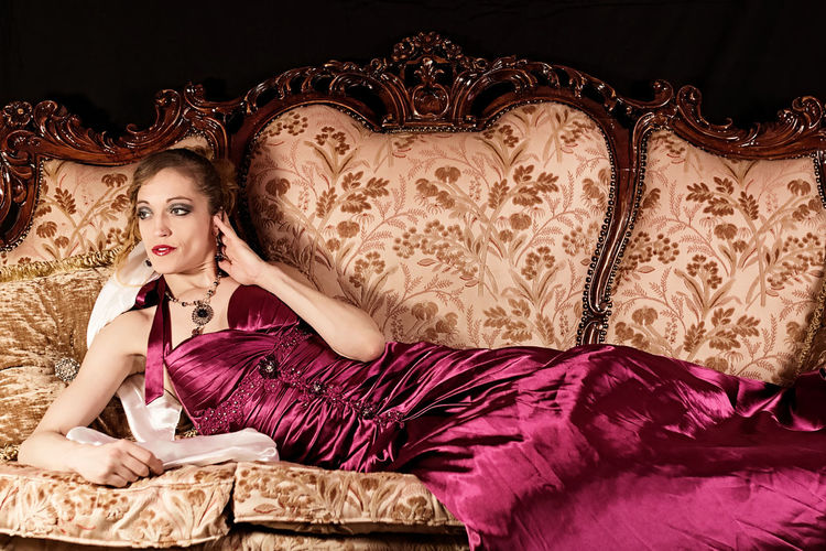 Glamour shot of beautiful and stylish woman lounging in antique couch. Dress Elegant Elégance Lifestyle Stylish Antique Furniture Beautiful People Beautiful Woman Beauty Fashion Fashion Model Glamour Indoors  Lifestyles Lounging Luxury Model Pink Dress Portrait