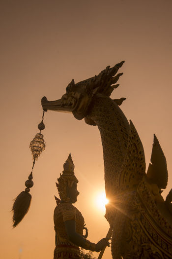 Low angle view of statue against sky at sunset