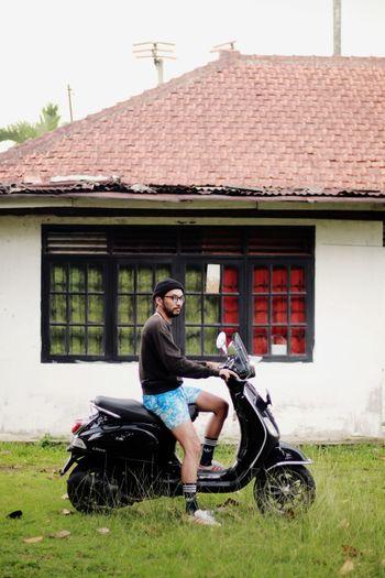 Full length of man sitting outside house against building