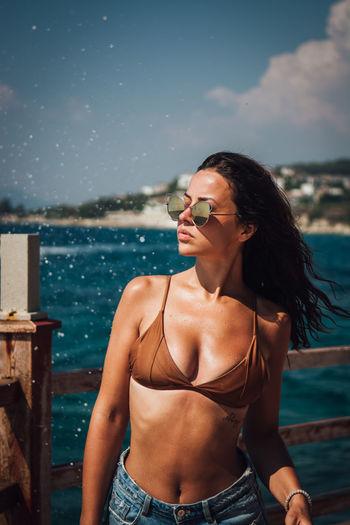 Beautiful Young Woman Wearing Bikini While Standing Against Sea At Beach
