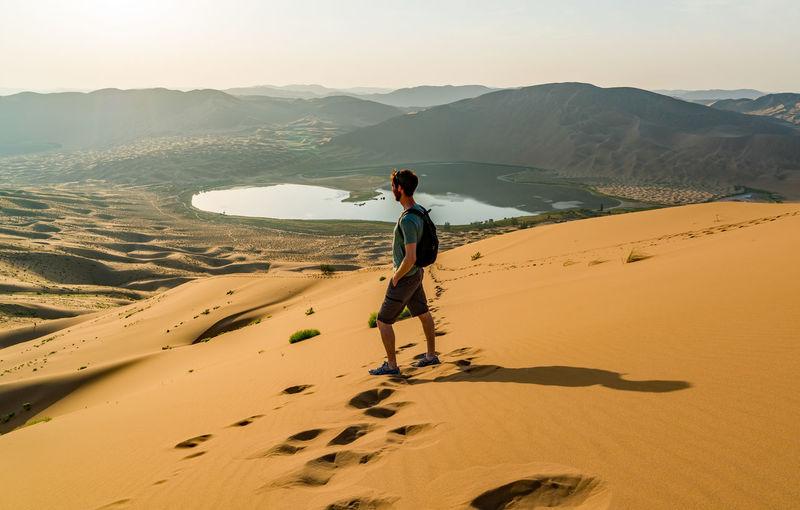 Man standing on sand dune at badain jaran desert