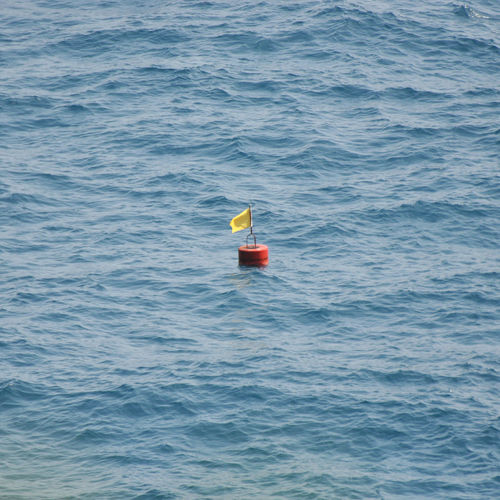 Yellow flag on the sea Beauty In Nature Boa Day Flag Floating On Water Minimalism Nature No People Outdoors Sea Sea View Tranquil Scene Tranquility Water Waterfront Yellow Flag