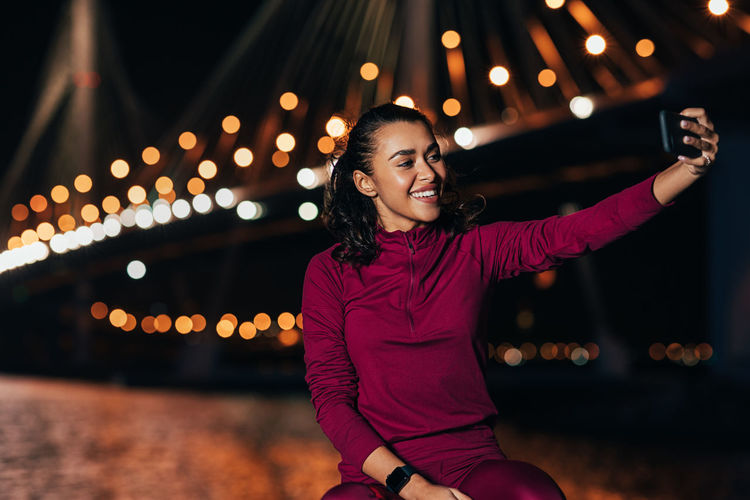 Smiling young woman standing against illuminated lights at night