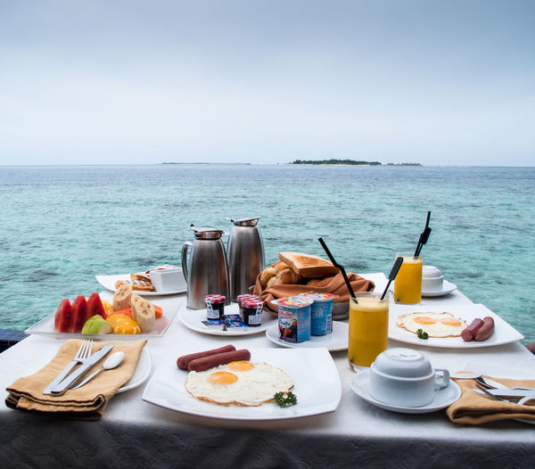 Food on table by sea against clear sky