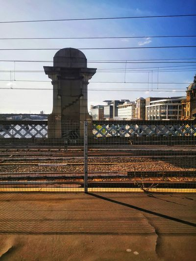 Railroad tracks by buildings against sky