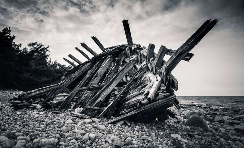 Ship Wreck On Shore Against Cloudy Sky