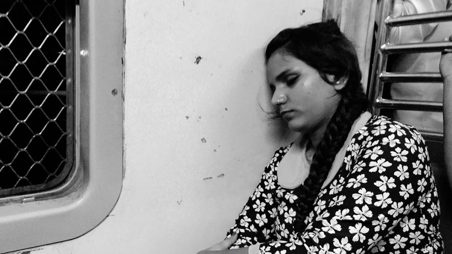 Young woman sleeping while traveling in train