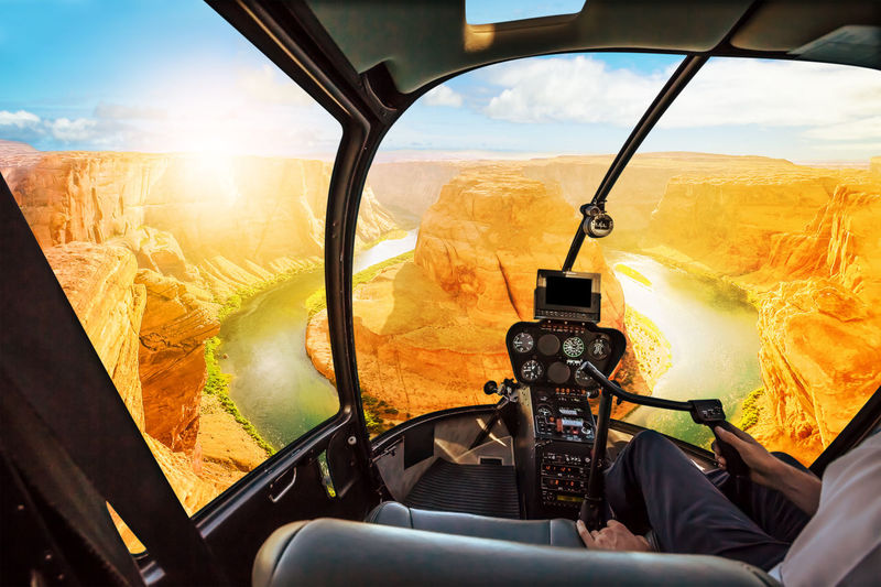 Helicopter cockpit scenic flight over Horseshoe Bend of Colorado River in Arizona, United States. Downstream from the Glen Canyon Dam and Lake Powell at sunset. United States Horseshoe Bend Horseshoe Bend, Utah Utah Sunset Colorado Colorado River Canyon USA America Aerial View Panorama Helycopter Flying Flight Vehicle Interior Mode Of Transportation Transportation Nature Sky Day Air Vehicle Cockpit Glass - Material One Person Window Sunlight Outdoors Cloud - Sky Transparent Environment Landscape Land Vehicle