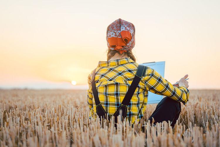 Farmer woman on wheat field doing admin regarding the past harvest