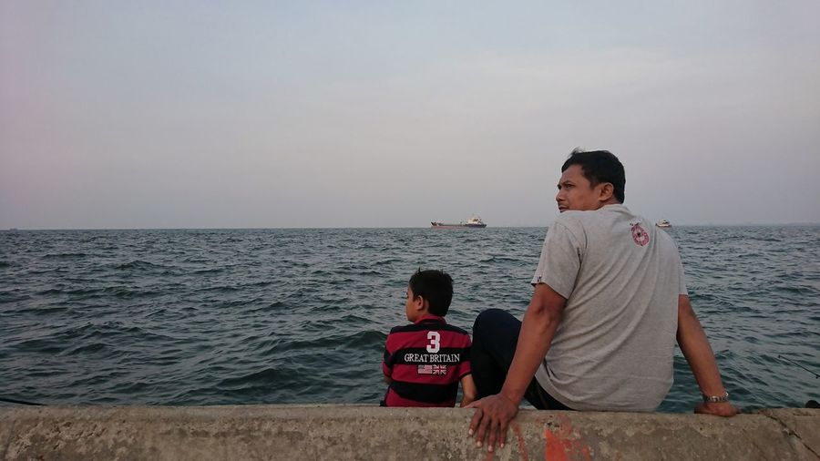 Rear view of men sitting by sea against sky