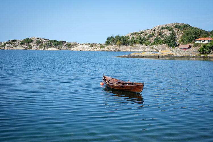 Boat See Calm Rowing Boat On Water Clear Sky Summer Day Coastline Scandinavia Sea Blue Outdoors