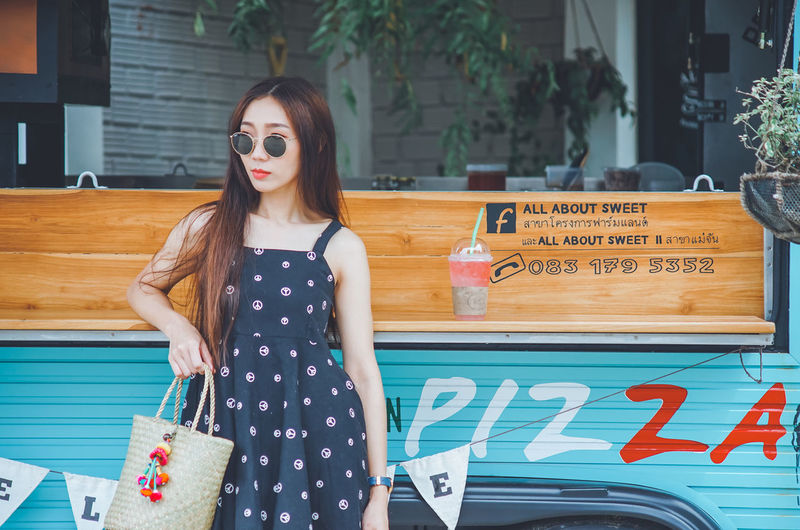 Young woman wearing sunglasses standing against food truck