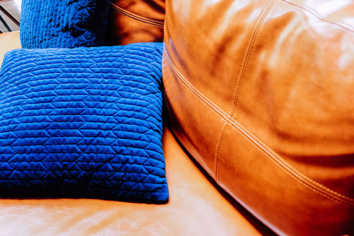Close up detail of blue pillow on leather sofa Decor Leather Living Orange Pillow Blue Brown Business Close-up Clothing Cushion Decoration Decorations Decorative Fashion Furniture Furniture Details Home Interior Indoors  Interior Design Jeans Leather Leather Sofa Living Room Midsection No People Orange Color Pattern Retail  Selective Focus Sofa Table Textile