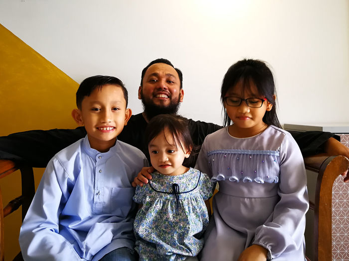 Portrait of happy family sitting at home on eid-ul-fitr