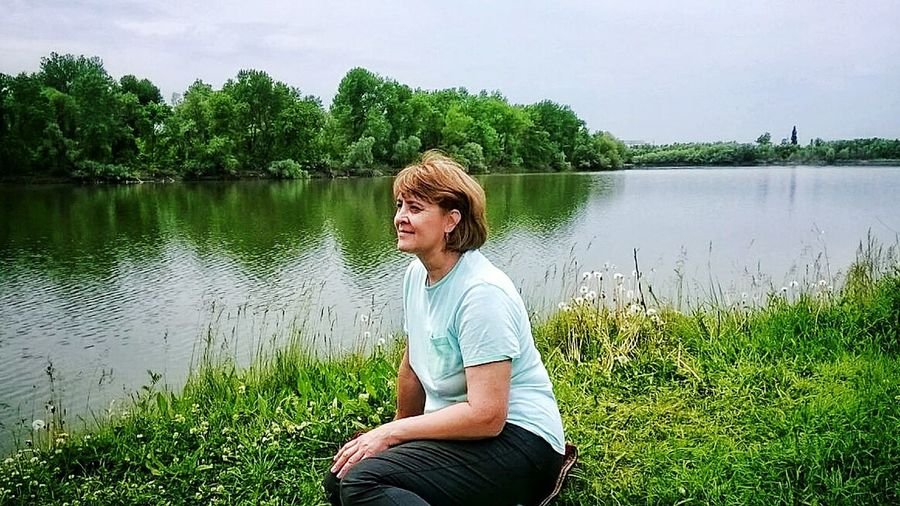 Woman sitting by lake against sky