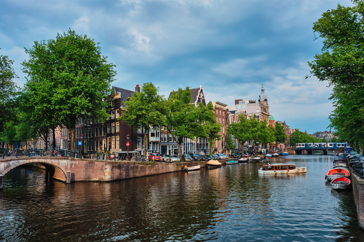 Scenic view of canal in city against sky
