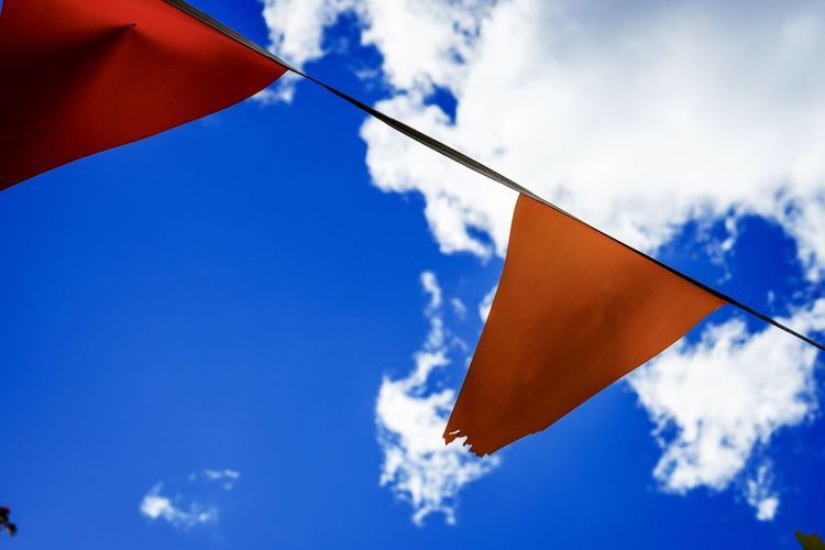 Close-up of flags against blue sky