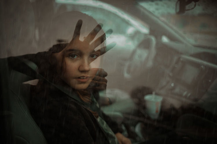 Portrait of girl seen through wet window