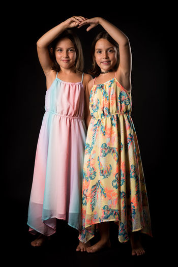 Portrait of girl standing with sister on black background