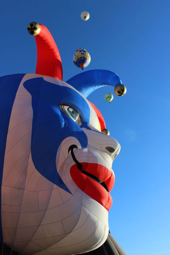 Low Angle View Of Inflatable Clown Head Against Clear Sky