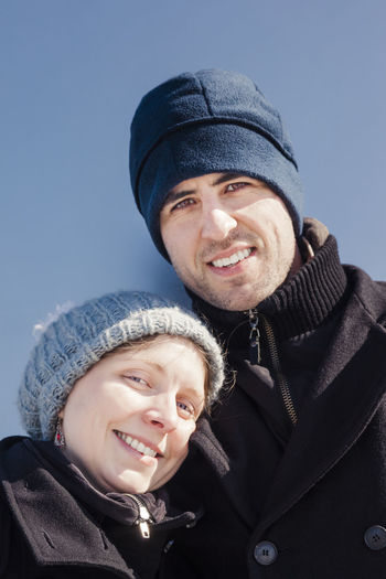 Portrait of couple smiling while standing against clear blue sky