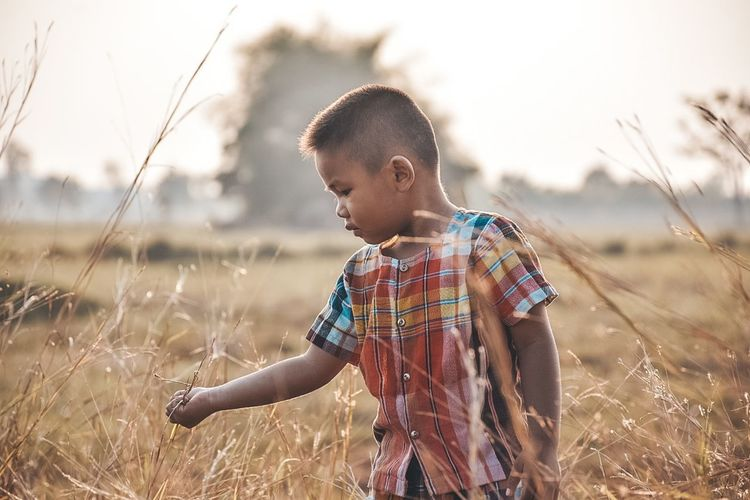 Boy standing on field against sky