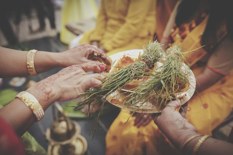 Midsection of woman holding religious equipment in plate during wedding ceremony