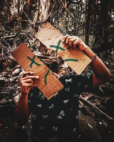 High angle view of woman reading book in forest