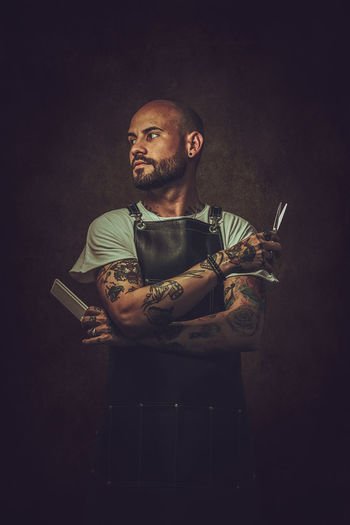 Man holding scissor  against black background