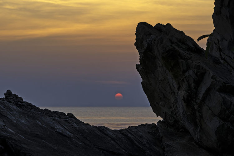 Rock formation in sea against sky during sunset