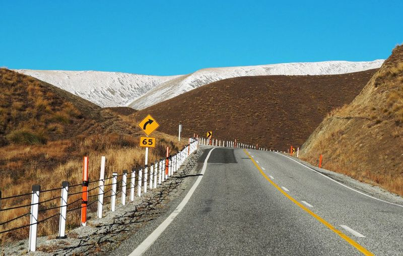 Road amidst mountains against clear sky