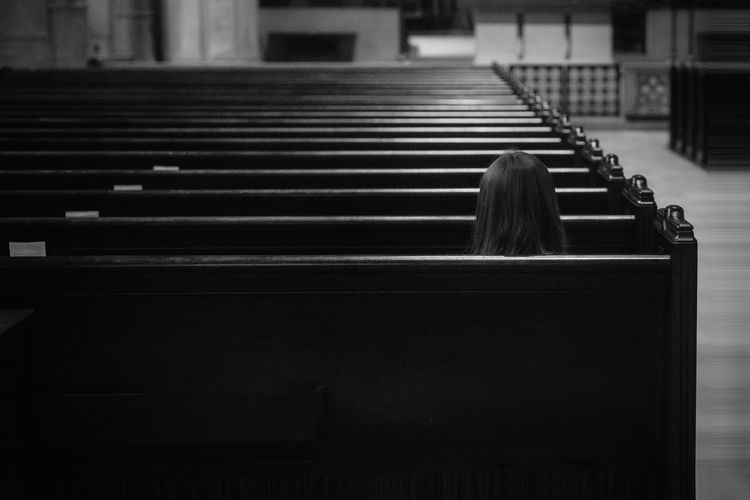 Rear view image of girl sitting in church facing alter