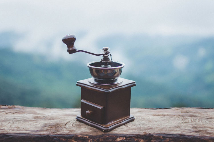Close-up of coffee grinder on table against sky