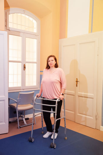Full length portrait of woman with mobility walker at home