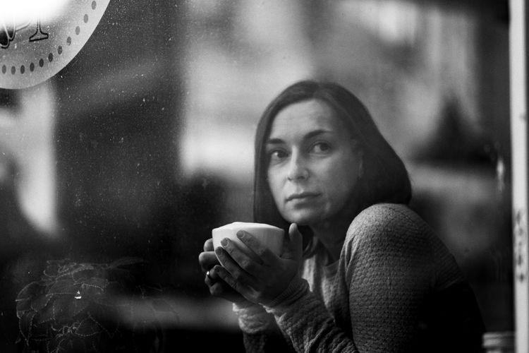 Beautiful woman looking through window while holding coffee cup at cafe