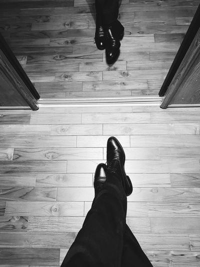 Low section of man wearing shoes on hardwood floor